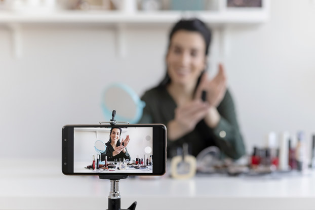 A smartphone on a tripod takes a video of a woman showing off various beauty products.