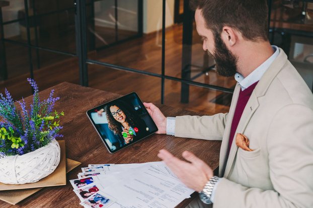 human resources manager interviewing a candidate in a video chat on a tablet