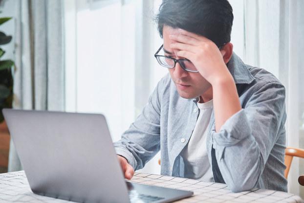 Worried man looks at laptop