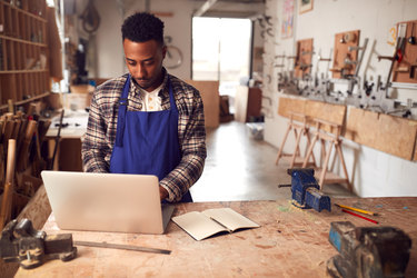 small business owner in studio working on laptop