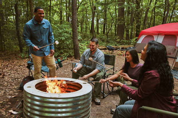 A group of friends roasts marshmallows around a metal firepit. They're sitting in foldable chairs in a forest clearing. A large tent is set up in the background.