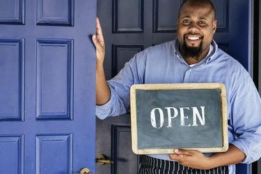 """A Black man stands in front of a set of large blue doors. He smiles as he holds a sign that reads """"OPEN."""""""