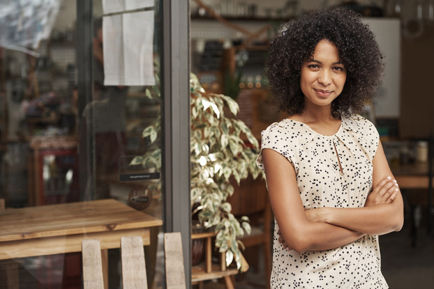 confident woman business owner standing outside a storefront
