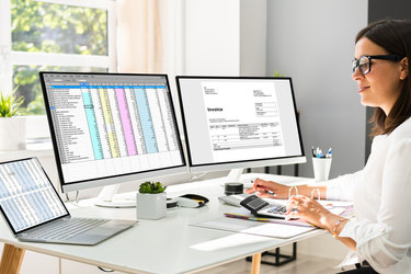 A woman consults a laptop and two computer monitors, which show spreadsheets and invoices. The woman types something on a calculator.