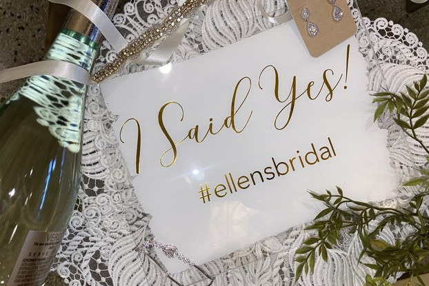 """""""I Said Yes!"""" sign with bridal earrings and a champagne bottle courtesy of Ellen's Bridal and Dress Shop."""