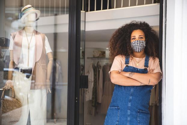 woman business owner wearing mask standing in doorway of her retail shop