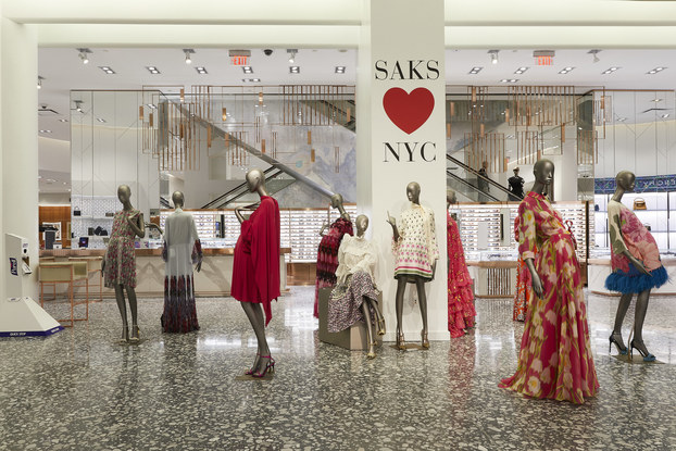 """Nine mannequins model bright summer dresses. Several of the mannequins are clustered around a column bearing the message """"SAKS HEARTS NYC."""""""