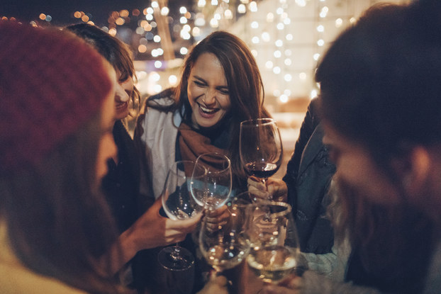 A group of girlfriends laughing and drinking wine together.