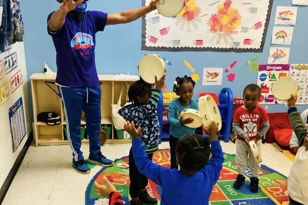 Move N Groove Kidz employee in a classroom working with young children.