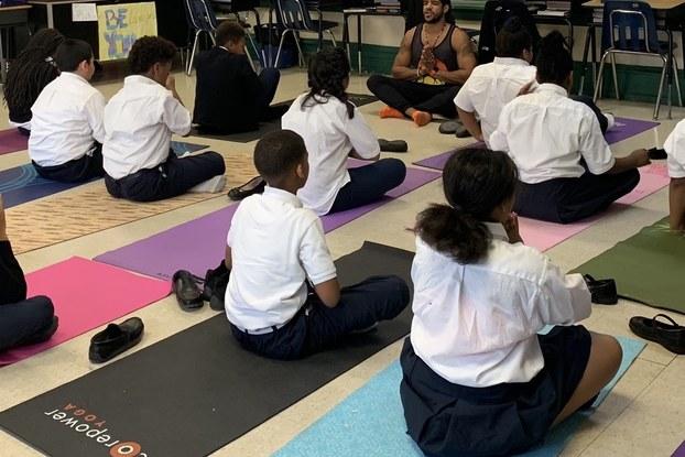 James Gaddy of Project Little Warriors teaching a yoga class of kids.