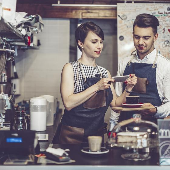 Baristas take a photo of latte art to promote cafe on social media.