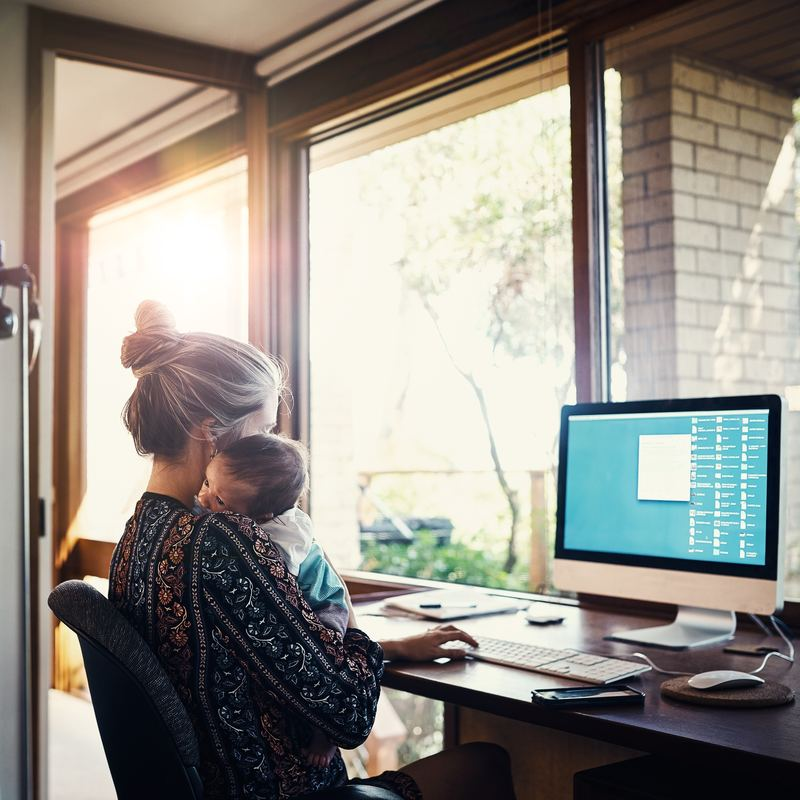 woman holding baby while working at home on laptop