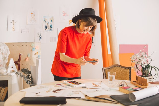 A woman in a bright orange shirt and black brimmed hat uses her smartphone to take a picture of art scattered on the table in front of her.