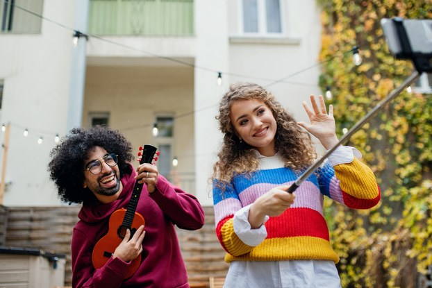 A woman in a multicolored striped sweater uses a smartphone on a selfie stick to film herself and a young man who plays a ukelele.