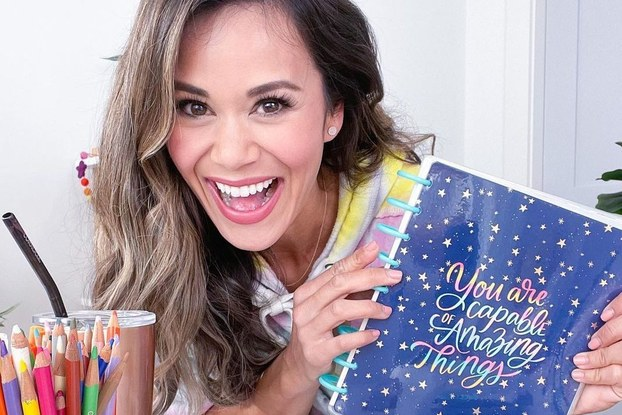 Brandi Milloy, Instagram influencer, holding a Happy Planner notebook.