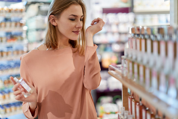 A woman in a beauty supply store smells perfume on her wrist. Shelves in the background and foreground hold bottles of perfume and other cosmetics.