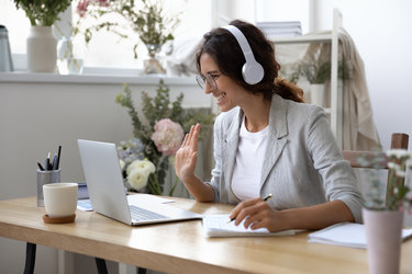 Woman greets virtual meeting attendees