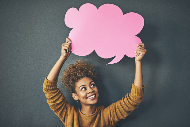 woman smiling holding speech bubble above her head.
