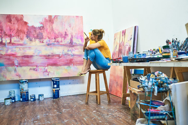 Woman artist sitting in her studio holding a paintbrush and looking at her painting.