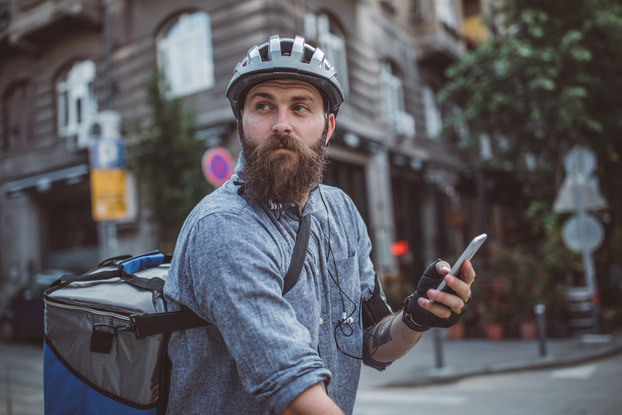 A bearded man in a city street intersection looks off-camera. He is carrying a cellphone and wearing a helmet and a large square backpack for carrying food. The photo is shot from the waist up, but the man is presumably sitting on a bike.