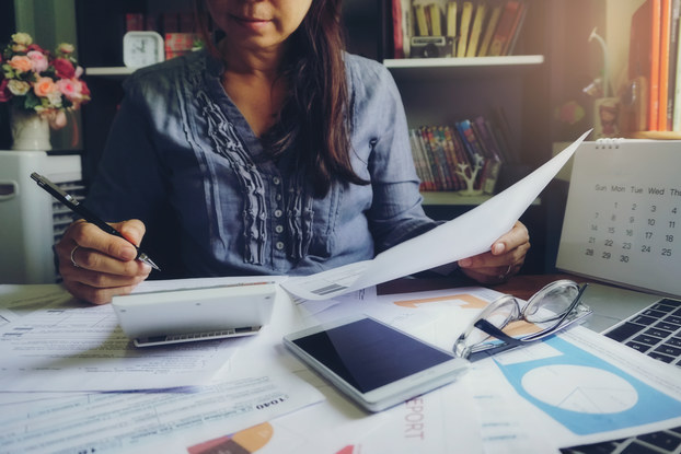 A woman, her face partially cut off in the photo, sits at a desk scattered with papers, a smartphone, and a laptop. She holds a paper and pencil and consults a calculator in front of her.