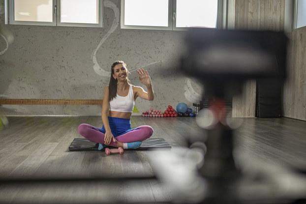Woman greets virtual fitness class participants