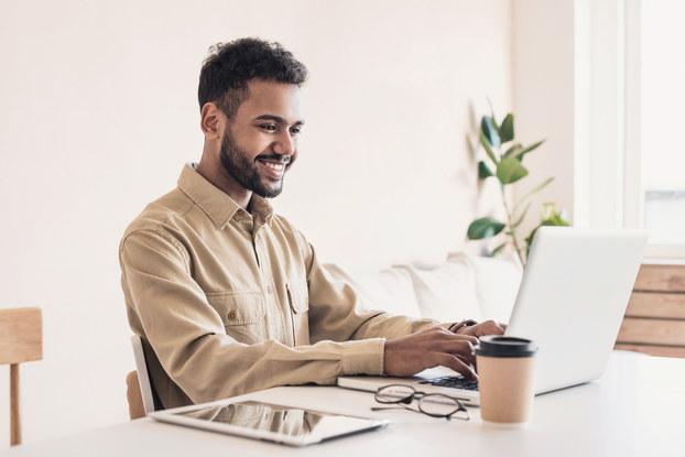 Man smiling while working on laptop.