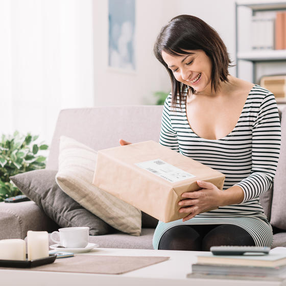 Happy woman holding a package while sitting on the couch.