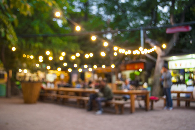 Blurred outdoor social area with picnic tables and bistro lights.