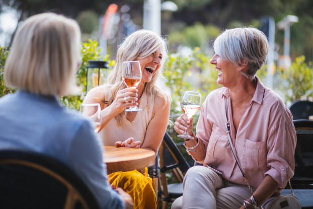 Women laugh over wine at an outdoor restaurant