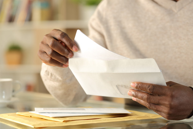 Close-up on a pair of hands opening a letter. A small pile of envelopes and manila folders sits on a table beneath the hands.