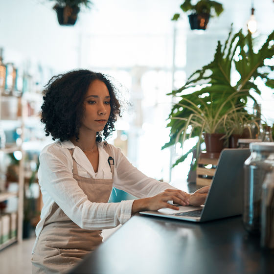 Woman business owner inside her business working on laptop.