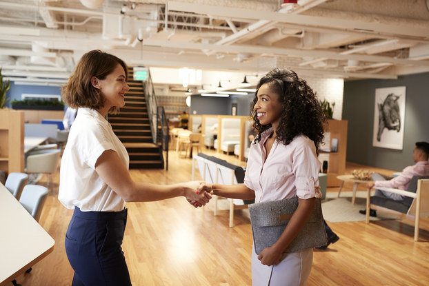 Two businesswomen meeting and shaking hands in modern office