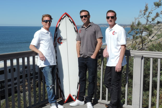 The leadership team behind Brah Electric, standing on a beachfront porch with a surfboard.