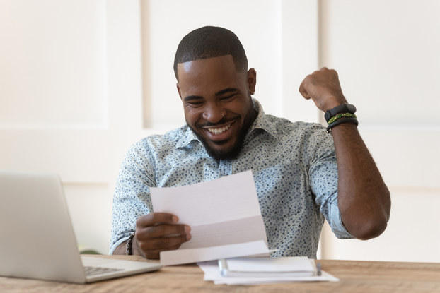 A man smiles and pumps his fist in response to something he reads on a piece of paper.
