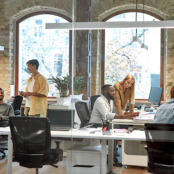 Team of employees sitting at desks inside a bright office.