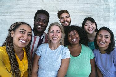 A diverse group of people stands shoulder-to-shoulder, smiling.