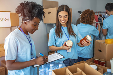 A group of people wearing light blue shirts and lanyards are boxing donations. One volunteer makes notes on a clipboard while another holds soup cans to be boxed. In the background, two more people look through a rack of clothes.