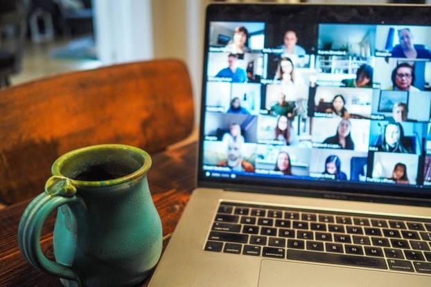Laptop screen showing a virtual Triple Coffee coffee tasting next to a mug of coffee.