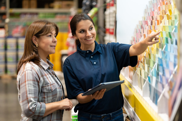 An employee at a home improvement store helps a woman pick out paint swatches. The employee holds a clipboard and points to some blue swatches.