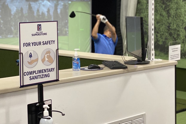 Golf simulator next to complimentary hand sanitizer at a PGA TOUR Superstore location.