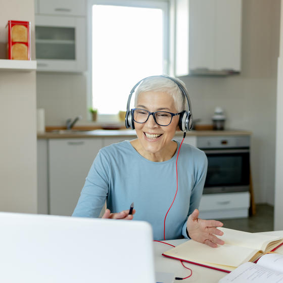 Woman working on headset and laptop in her dining room.