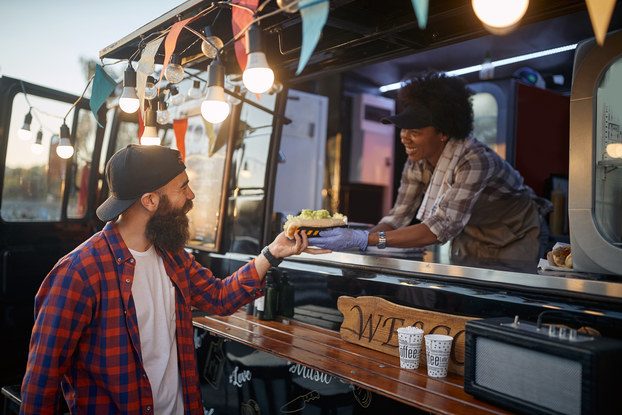 Customer purchasing food from the owner of a food truck.