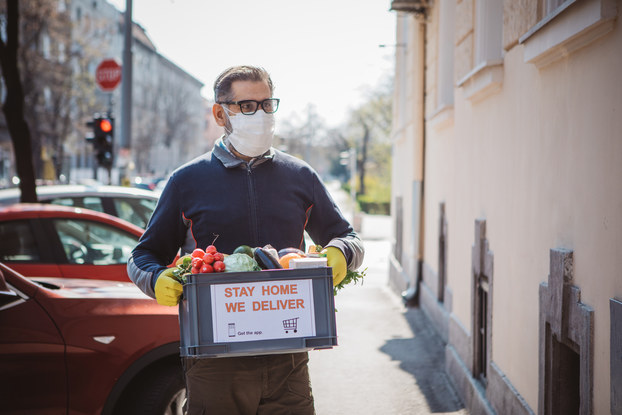 """A man wearing a face mask and rubber gloves carries a box of vegetables away from a line of parked cars. A sign on the box reads """"STAY HOME. WE DELIVER."""""""