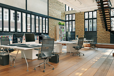 Modern office setting with desks and large windows.