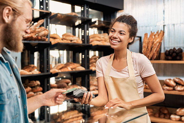 A man and a woman stand in a bakery in front of shelves piled with different kinds of bread. The woman wears an apron and holds out a credit card reader for the man, who scans his credit card.