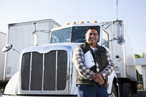 A man with a clipboard under one arm stands smiling in front of the cab of an 18-wheel truck.