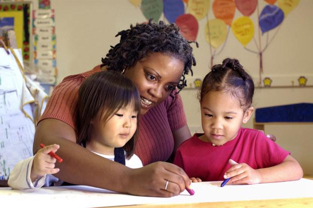 Daycare teacher draws with children