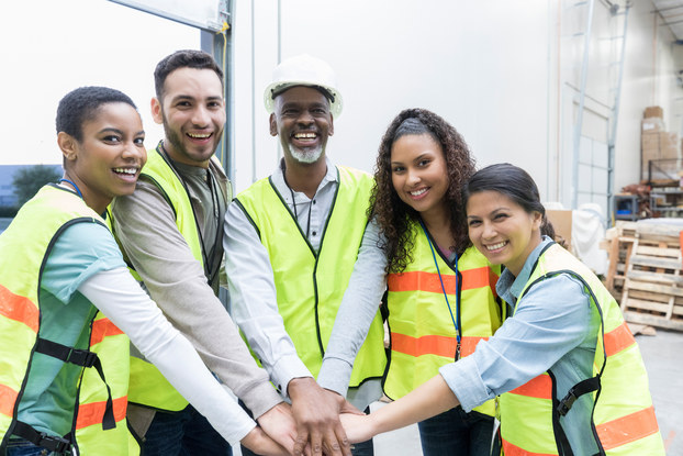 A group of employees of various ages, races, and genders stands in a semicircle with their hands together in the middle. They wear neon vests and smile for the camera.
