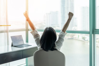 Woman sitting at desk with her back to the camera and her arms in the air with excitement.